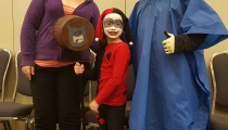 Harley Quinn is ready to take out Batman while Joker and Yorick watch proudly from afar.